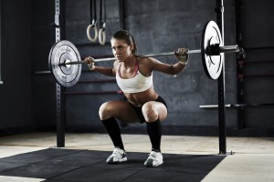 Active young woman lifting weight